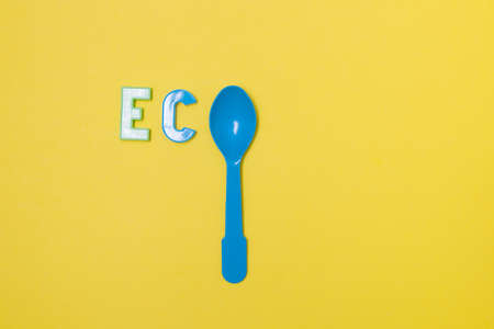 the inscription from the plastic letters eco, instead of the letter o - a plastic blue disposable spoon, yellow background, copy space, top view