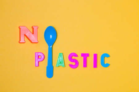 the inscription from plastic letters there is no plastic, instead of the letter o and the letter l - a plastic blue disposable spoon, yellow background, copy space, top view