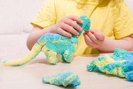 the child plays plasticine from polymer granules at the table, the original plasticine from tiny balls, the child plays with a dinosaur from plasticine, what to play with the child at home Stock fotó