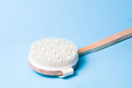 wooden brush for dry body massage on a light blue background, copy space, brush made of natural material with massage inserts
