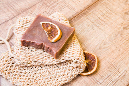 cocoa soap made from natural ingredients on a knitted washcloth, homemade soap and slices of dried orange on a wooden background, zero waste life style concept