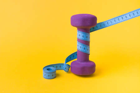 1.5 kilogram purple dumbbell and blue measuring tape on a yellow background, a dumbbell wrapped in a folded tape copy space, weight loss concept