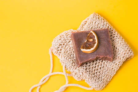 homemade cocoa soap on a knitted washcloth with a slice of dried orange on a yellow background copy space top view