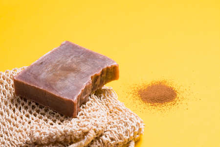 a piece of homemade chocolate soap and a knitted washcloth, a handful of ground coffee on a yellow background, chopped soap with cocoa