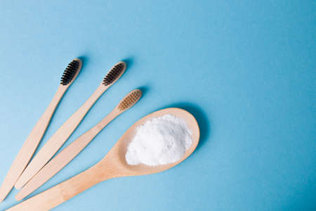 three different bamboo brushes and a wooden spoon with soda on a blue background, top view copy space, eco friendly lifestyle concept