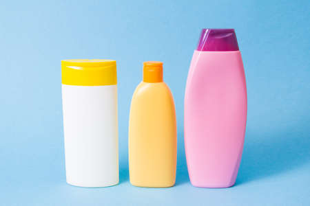 three different plastic bottles without labels for shampoo and shower gels on a blue background Imagens