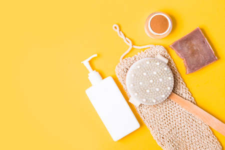 white bottle with dispenser without a label, a brush for dry massage, a jar of ground coffee, a knitted cotton washcloth, natural cocoa soap on a yellow background, top view, copy space
