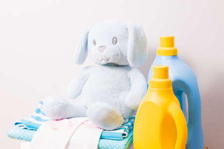 washing gel and fabric softener in bright plastic bottles of yellow and blue colors, a stack of colored children's clothes and a toy, clothespins for drying on a bright background