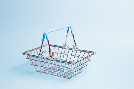 small toy basket on a light blue background, copy space, shopping concept