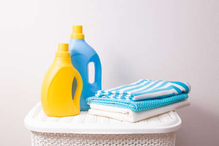 a stack of colored laundry and washing gels in yellow and blue bottles on a white plastic basket for dirty laundry, copy space, light background, washing colored clothes concept Imagens