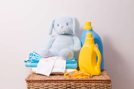 washing gel and fabric softener, a stack of colored children's underwear and a children's toy, clothes pegs for drying on a wicker basket for dirty clothes