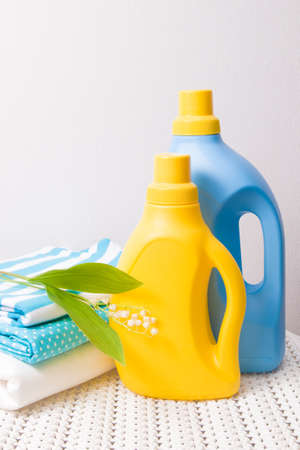 colored fabric clothes, lily of the valley flower, washing gel and fabric softener on a captive basket, yellow and blue bottles for gel without labels