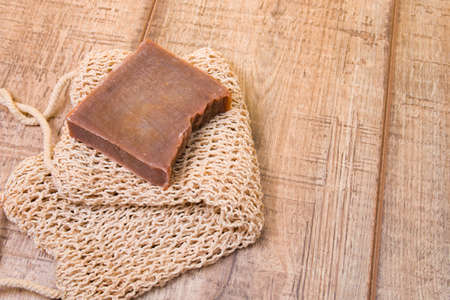 cocoa soap made from natural ingredients on a knitted washcloth, homemade soap on a wooden background, zero life-style waste, cocoa bar on a cotton thread washcloth