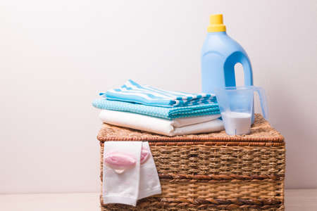 clothes in light blue tones, strange powder in a measuring cup and gel for washing colored clothes in a blue plastic bottle on a wicker laundry basket, children's socks stick out of the basket