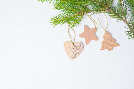 wooden Christmas toys in the shape of a heart and stars on a fucking background, fir branches and eco friendly Christmas toys, top view copy place Фото со стока