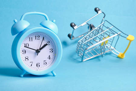alarm clock and miniature shopping trolley on blue background copy space