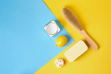 Professional eco cleaning, loofah, sponge, wood brush, natural soda, lemon on yellow-blue background, copy space. Gentle cleaning concept