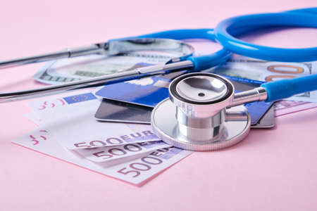 stethoscope, credit cards and euro banknotes on pink background, concept of impact of coronavirus pandemic and crisis on exchange rates