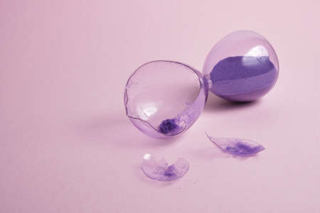 broken glass hourglass with purple sand on a pink background, time concept