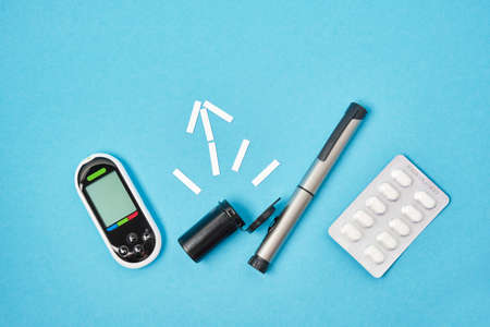 pills, glucose meter and syringe pen for injections of insulin on a blue background, test strips for measuring blood sugar in the shape of an arrow top view place copy