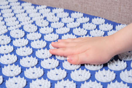 baby palm on a blue massage acupuncture mat with white massage tips, massage mat for relaxation and treatment Banque d'images