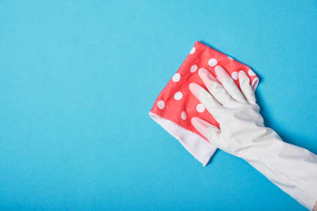 hand in white rubber glove holds pink polka dot rag, blue background copy space