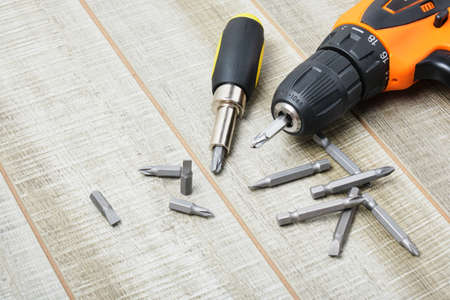 electric screwdriver, self-tapping screws, screwdriver bits, tool box on a wooden background copy space