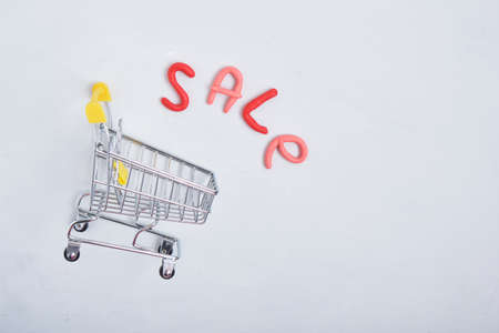 inscription sale and shopping trolley on gray background copy space