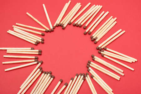 frame of matches in the shape of a circle on a red background copy space