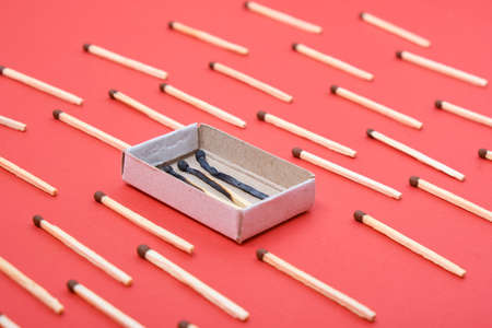 pattern of matches and a box of burnt matches on a red background top view