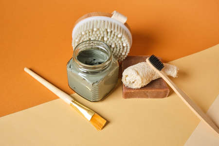 loofah, soap, blue clay in a jar, massage brush, brush and bamboo toothbrush on brown background, copy space