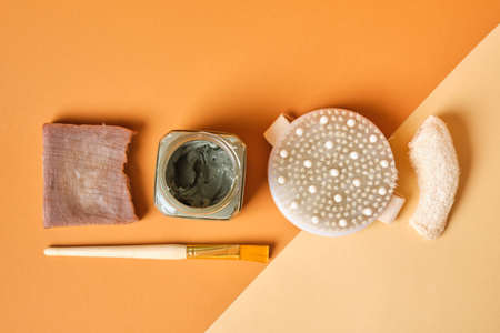 loofah, soap, blue clay in a jar, massage brush and brush on brown background, copy space top view