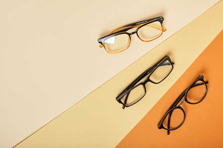 several pairs of glasses on beige and brown background, geometric background top view copy space