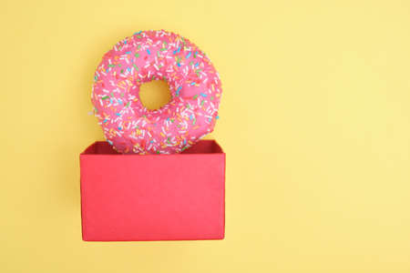 donut with sprinkles and pink icing in a gift box on a yellow background top view copy space