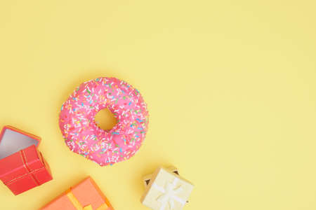 donut with sprinkles and pink icing and several different gift boxes on a yellow background top view copy space