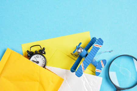 toy model of a vintage plane made of metal, several parcels, an alarm clock and a magnifying glass on a blue background, air mail concept, tracking mailings concept