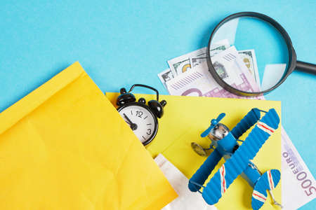 toy model of a vintage airplane made of metal, cash, several parcels, alarm clock and magnifier on blue background, air mail concept, tracking mailings concept