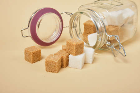 brown and white sugar cubes fell out of a jar with a sealed lid, beige background