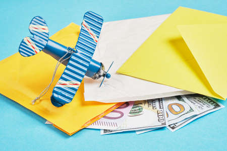 toy model of a vintage plane made of metal, money, several parcels and several banknotes on a blue background, air mail concept, tracking mailings concept