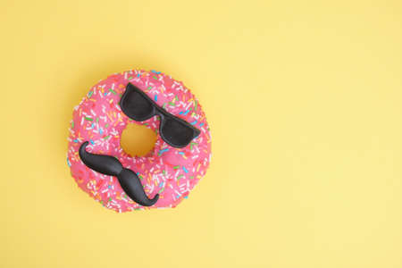 donut with sprinkles and pink icing, donut with mustache and glasses, fun minimalistic food concept, foodporn, yellow background top view copy space