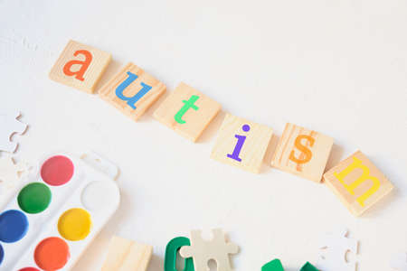 watercolor paints and children's educational toys on a light background, the inscription autism on wooden squares, treatment and diagnosis of autism concept