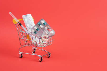 Shopping cart with medicine on red background. The concept of medicine and the sale of drugs. Copy space. buy medicines online and at the pharmacy