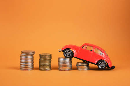 several stacks of coins and a small red car on a brown background, buying and selling a car concept copy space