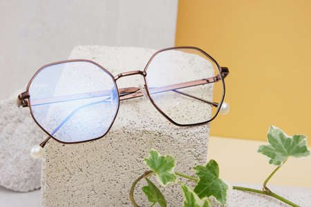 eye glasses on a concrete podium on a beige background, trend composition, stylish eye glasses on a beige background with plants and tiles copy space Stockfoto