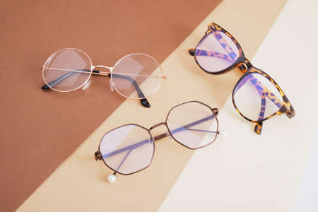 several trendy stylish pairs of eye glasses on a geometric background of different shades of brown optics concept