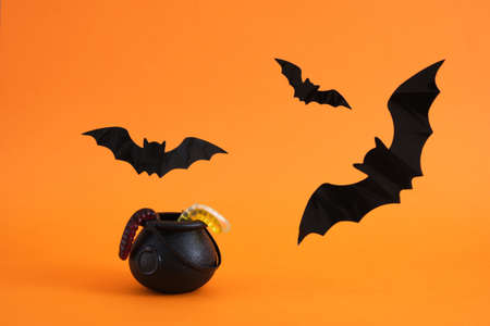 halloween decoration concept small decorative witch cauldron, gummy worms, spiders, cobwebs and bats on orange background, halloween background Banco de Imagens