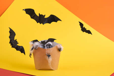 fast food packaging for fries with cobwebs and spiders, decorative bats, halloween concept, yellow background halloween decoration concept Banco de Imagens