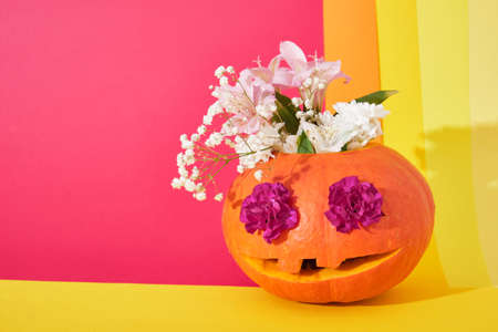 pumpkin jack lantern with flowers inside on colored background, halloween concept, day of the dead background flowers in the eyes of a pumpkin