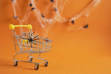 shopping cart with spider on brown background, halloween shopping on concept, cobwebs and spiders on background copy space Banco de Imagens