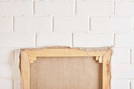 Blank square canvas against white brick wall. Mockup. inverted canvas